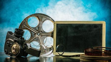 rollo pelicula: Retro accesorios de producción de películas de naturaleza muerta. negro de la tarjeta en blanco para copyspace. Concepto de la cinematografía. efecto sobre el fondo del humo