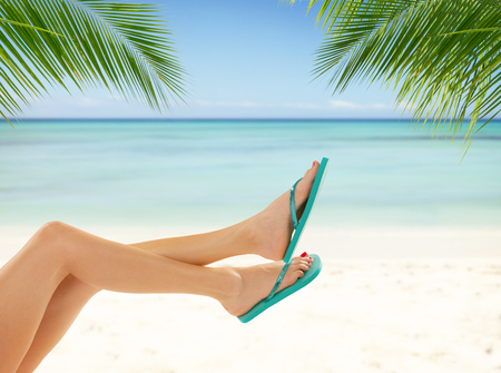 women legs: Sexy smooth woman legs with tropical beach on background. Cosmetics concept for summer Stock Photo