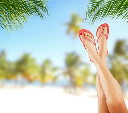 Sexy gladde vrouw benen met tropisch strand op de achtergrond. Cosmetica concept voor de zomer Stockfoto