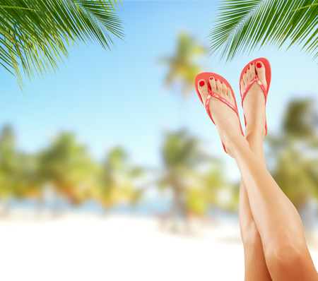 Sexy smooth woman legs with tropical beach on background. Cosmetics concept for summer Stock Photo