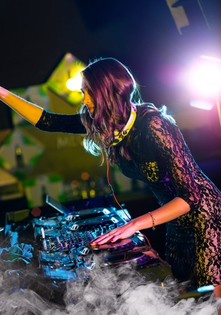 electronic music: Disc jockey brunette girl mixing electronic music in club