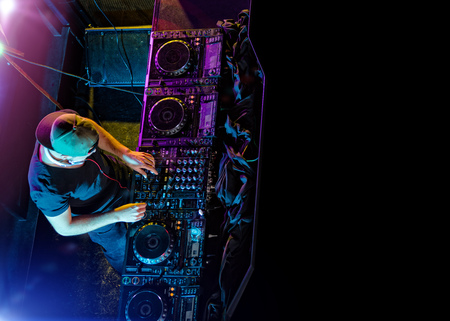 Disc jockey mixing electronic music in club. Shot from aerial percspective. Copyspace for text