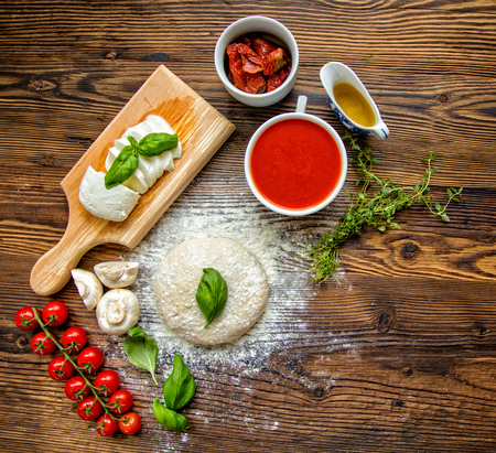salsa de tomate: Pizza dough with ingredients and tomato sauce served on rustic wooden table. Aerial shot, copyspace for text