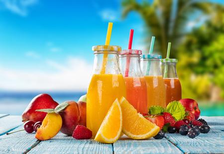 Vetri freschi di succo con mix di frutta immessi sulla spiaggia su assi di legno. Concetto di bevande salutari, antiossidanti e cocktail estivi.