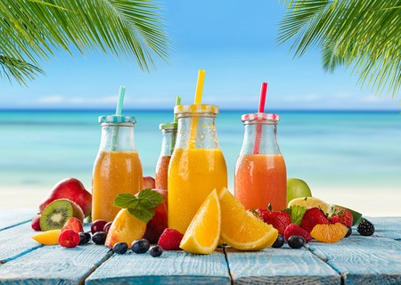 Fresh glasses of juice with fruit mix placed on the beach on wooden planks. Concept of healthy drinks, antioxidants and summer cocktails. Standard-Bild
