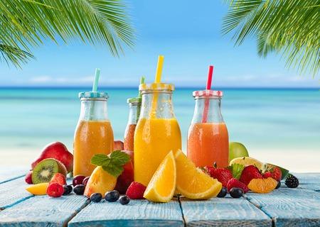batidos frutas: vasos de jugo fresco con la mezcla de frutas colocadas en la playa en tablones de madera. Concepto de bebidas saludables, antioxidantes y cócteles de verano.