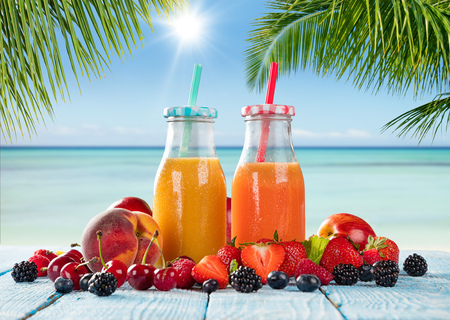energy mix: Fresh glasses of juice with fruit mix placed on the beach on wooden planks. Concept of healthy drinks, antioxidants and summer cocktails. Stock Photo