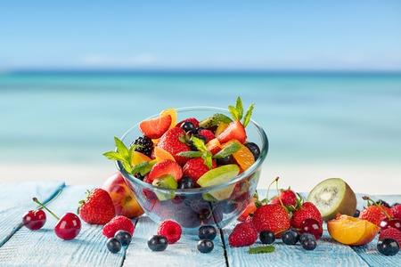 ensalada de frutas: Ensalada de fruta fresca colocada en tablones de madera, mancha en el fondo del mar. Concepto de alimentación saludable, antioxidantes y el horario de verano.