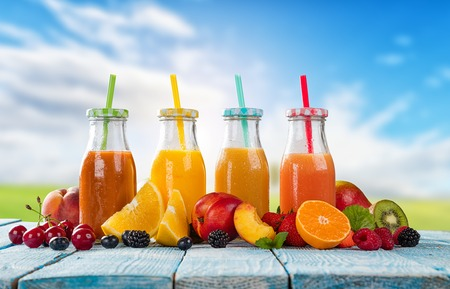 energy mix: Fresh glasses of juice with fruit mix placed on wooden planks. Blue sky on background. Concept of healthy drinks, antioxidants and summer cocktails. Stock Photo