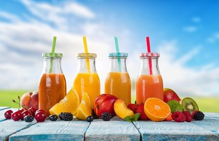 cocteles de frutas: vasos de jugo fresco con la mezcla de frutas colocadas en tablones de madera. cielo azul en el fondo. Concepto de bebidas saludables, antioxidantes y cócteles de verano.