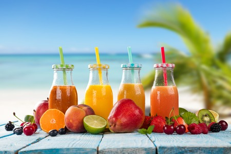 cocteles de frutas: Fresh glasses of juice with fruit mix placed on the beach on wooden planks. Concept of healthy drinks, antioxidants and summer cocktails. Foto de archivo