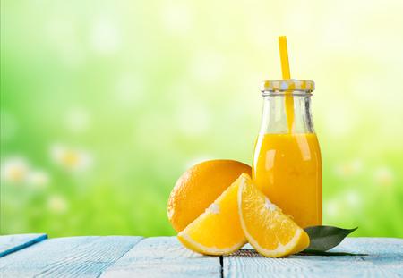 cocteles de frutas: fresco vaso de jugo de naranja con la fruta colocada en tablones de madera. desenfoque en el fondo del jardín. Concepto de consumo saludable, antioxidantes y cócteles de verano.