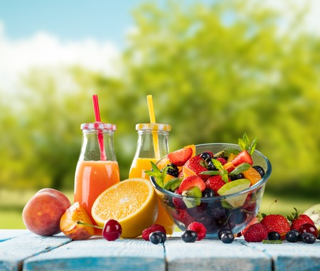 summer fruit: Fresh glasses of juice and salad with fruit mix placed on wooden planks. blur garden on background. Concept of healthy eating, antioxidants and summer cocktails. Stock Photo