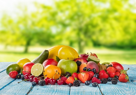 mix fruit: Fresh fruit pile placed on wooden planks, blur garden on background. Concept of healthy eating, antioxidants and summer time. Stock Photo