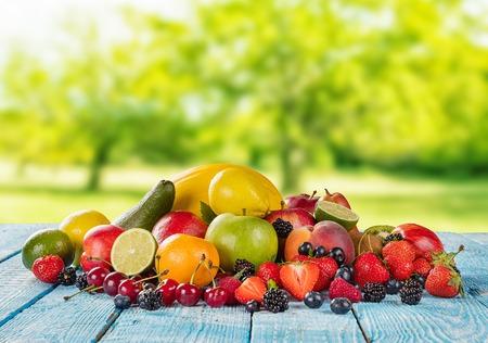 ensalada de frutas: montón de fruta fresca colocada en tablones de madera, jardín de desenfoque en el fondo. Concepto de alimentación saludable, antioxidantes y el horario de verano.