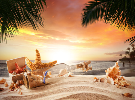 white sand beach: Sandy tropical beach with shells, bottle with message and starfish in beautiful sunset light
