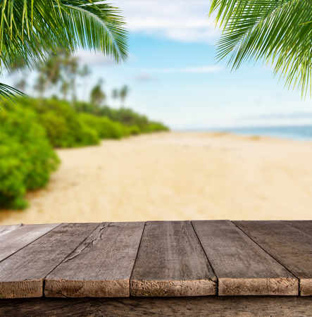 product placement: Empty wooden planks with blur beach on background, can be used for product placement, palm leaves on foreground