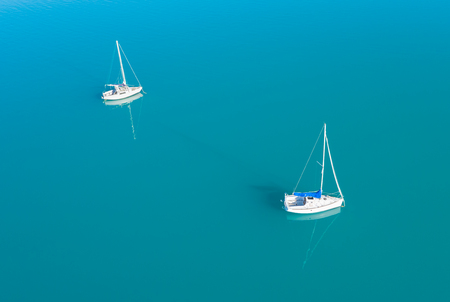 Beautiful aerial view of two yachts sailling on azure water