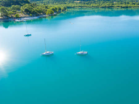 sailling: Beautiful aerial view of three yachts sailling on azure water. Coastal shore on background Stock Photo