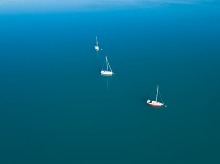 Beautiful aerial view of three yachts sailling on azure water