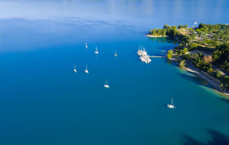 sailling: Beautiful aerial view of yachts sailling on azure water. Coastal shore on background