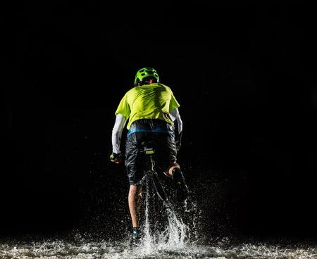 Mountainbiker 's nachts rijden door bosstroom en spatten water rond. Backside-view Stockfoto