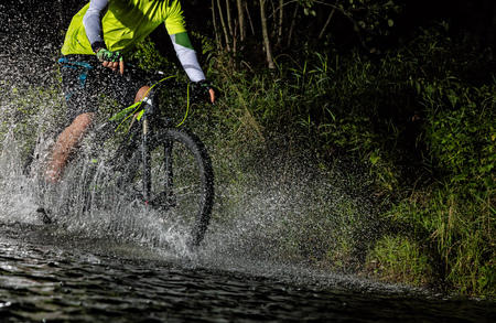 Mountain biker at night riding through forest stream and splashing water around. Close-up of side view