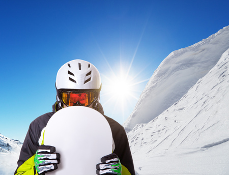 piste: Snowboarder holding his snowboard off piste, beautiful winter landscape panorama on background
