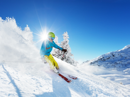 piste: Skier on piste running downhill in beautiful Alpine landscape. Blue sky on background. Free space for text Stock Photo