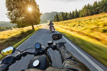 handle bars: Motorcycle drivers riding on motorway in beautiful sunset light. Shot from pillion driver view Stock Photo