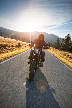 touring: Motorcycle driver riding on motorway in beautiful sunset light. Shot from front view