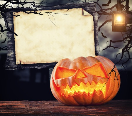 Scary halloween pumpkin with empty wooden sign board for copyspace