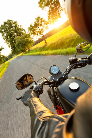 touring: Motorcycle driver riding on motorway in beautiful sunset light. Shot from pillion driver view