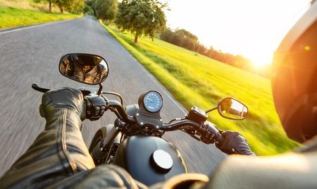 아름다운 석양 빛에 고속도로를 타고 오토바이 드라이버. 여성용 안장 드라이버보기에서 총