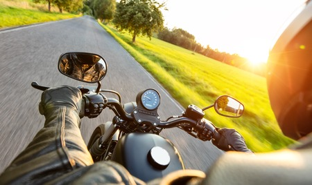 pilote de moto sur l'autoroute dans la belle lumière du soleil couchant. Prise de vue du conducteur passager