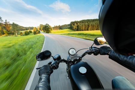 manejar: conductor de la motocicleta que monta en la autopista a la luz hermosa puesta de sol. Disparo de la vista del conductor acompañante
