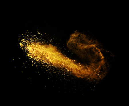 black ink: Explosion of yellow powder, isolated on black background