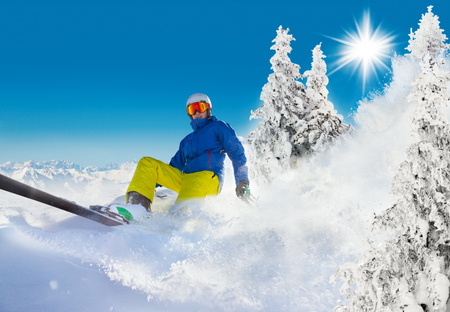 Skier on piste running downhill in beautiful Alpine landscape. Blue sky on background. Free space for text Stock Photo