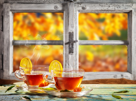 Autumn still life with tea cups on wooden planks, placed in front of wooden window. Cozy home interior.