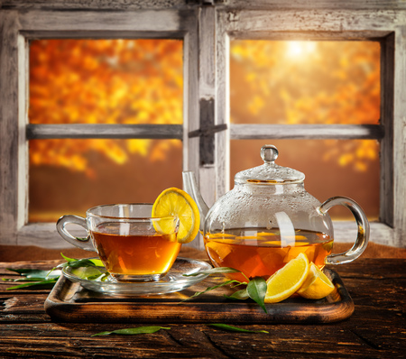 wooden window: Autumn still life with tea cup on wooden planks, placed in front of wooden window. Cozy home interior. Stock Photo