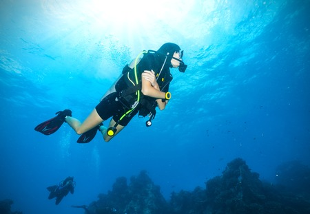 Young woman scuba diver exploring sea bottom. Underwater life with beautiful rocks and coral