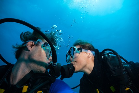 Couple of scuba divers kissing each other underwater Stock Photo