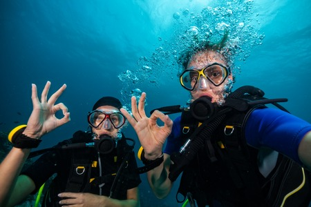 Couple of scuba divers showing OK signal underwater
