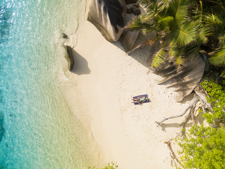 anse source d argent: Aerial photo of Seychelles tropical beach Anse Source D Argent at La Digue island with young woman sunbathing Stock Photo