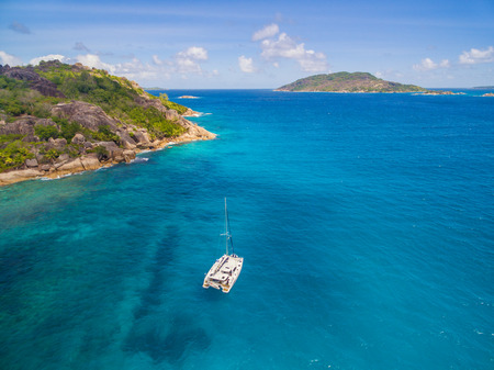 Aerial view of catamaran sailling in coastline. Tropical Seychelles island on background