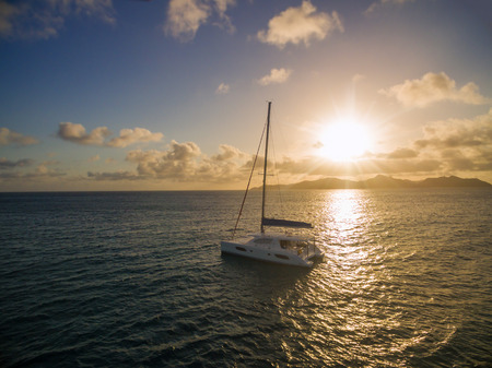 Aerial view of catamaran sailling in coastline with beautiful sunset. Tropical Seychelles island on background