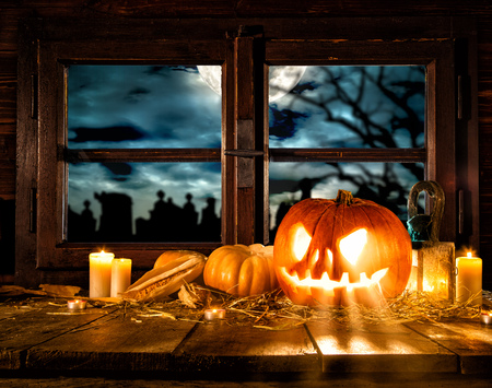 copysapce: Scary halloween pumpkin on wooden planks, placed in front of window with scary background Stock Photo
