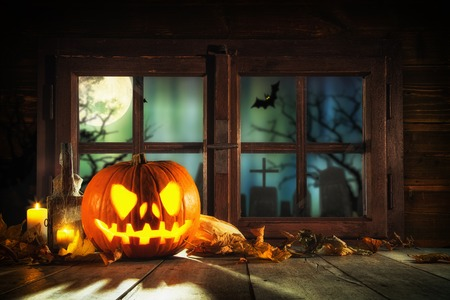 Scary halloween pumpkin on wooden planks, placed in front of window with scary background Stock Photo
