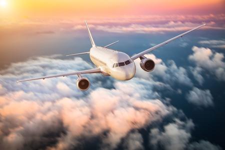 Aereo di linea volare sopra le nuvole in luce drammatica tramonto