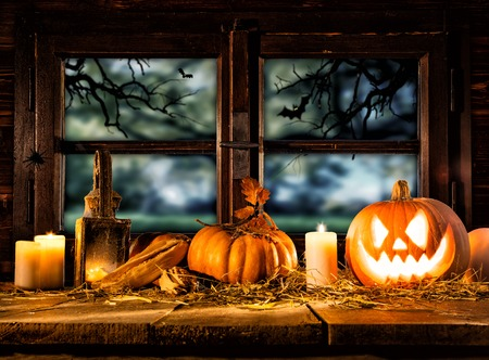 copysapce: Scary halloween pumpkins on wooden planks, placed in front of window with scary background Stock Photo
